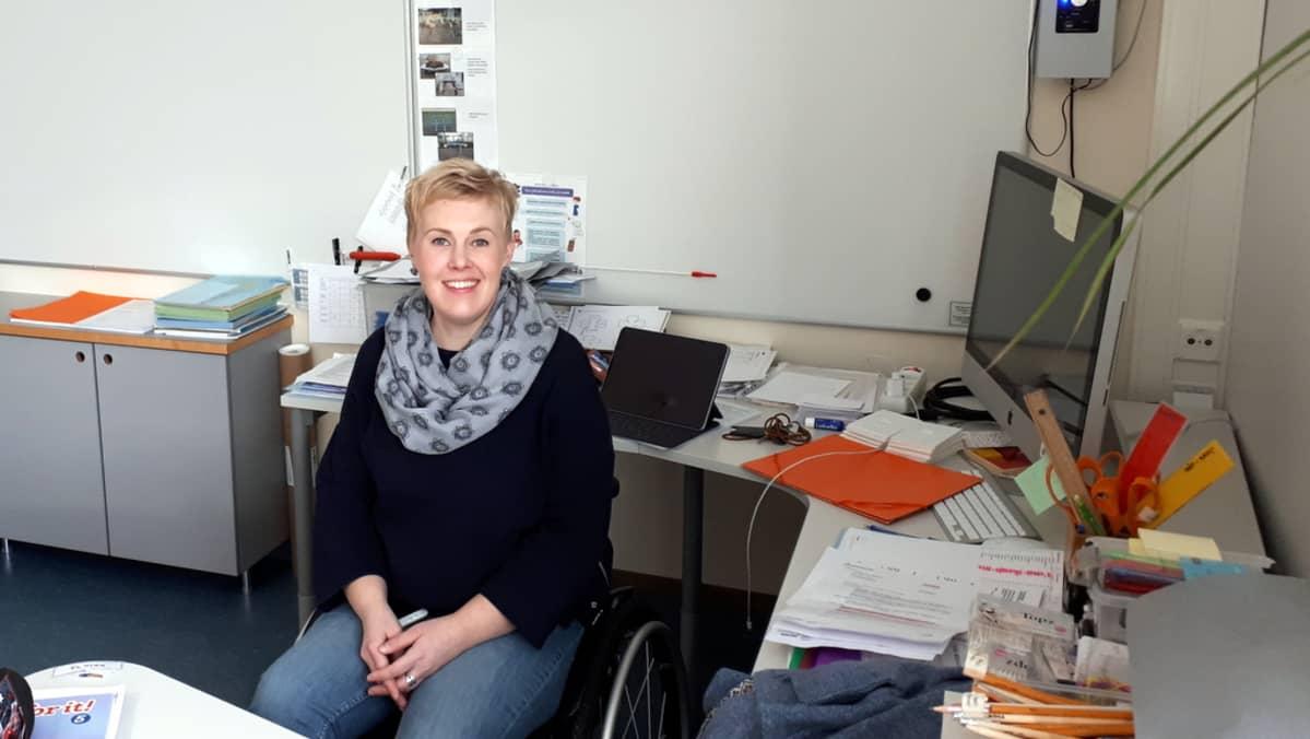 Opettaja Jenni Koskinen pyörätuolissa opettajanpöydän takana