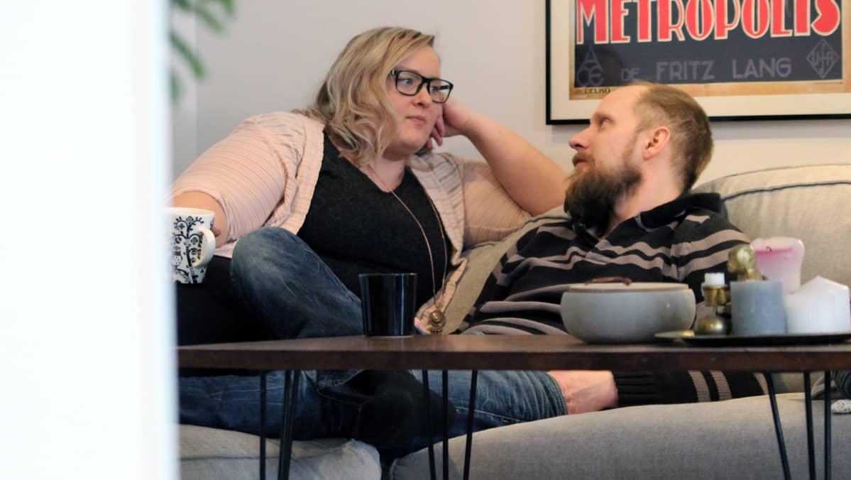 Tanja Rongas ja Tomppa Ojava keskustelemassa olohuoneensa sohvalla kahvikuppien äärellä