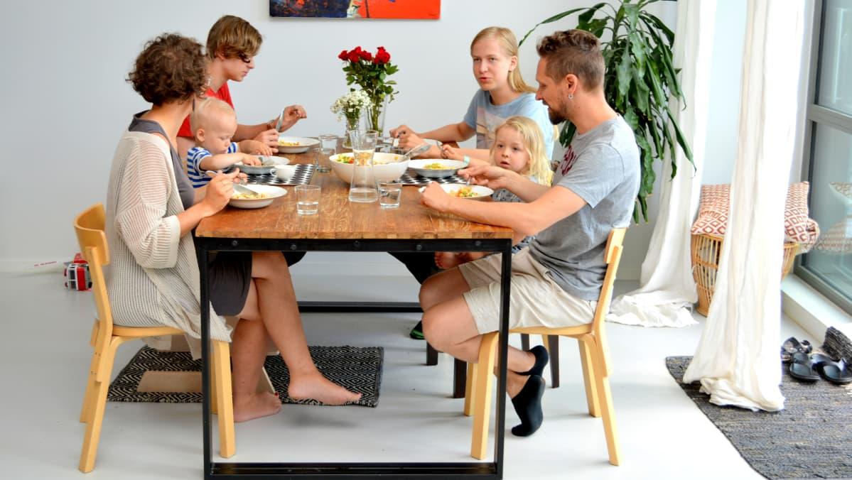 Lapsiperhe koolla yhteisellä aterialla.