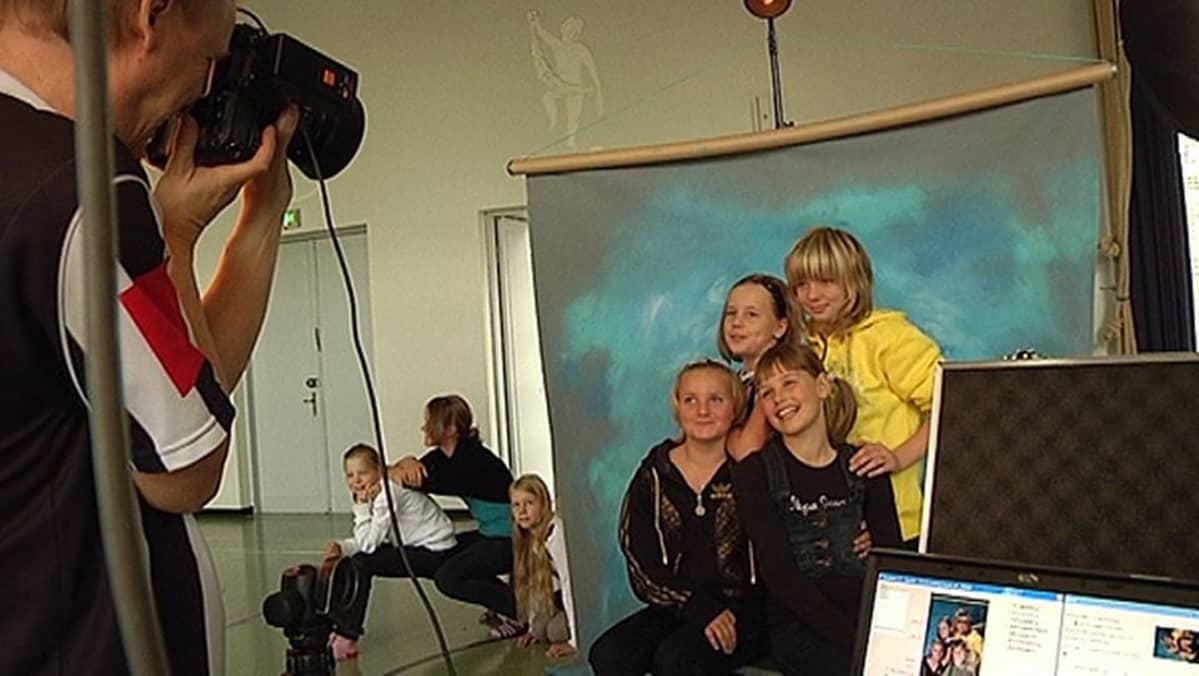 Valokuvaaja ottaa kaverikuvaa neljästä ystävästä.