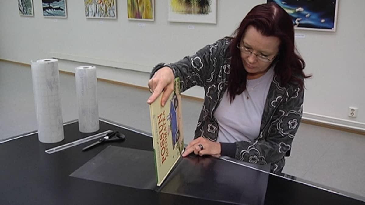 Kirjastovirkailija sovittelee kirjaa päällystemuoviin