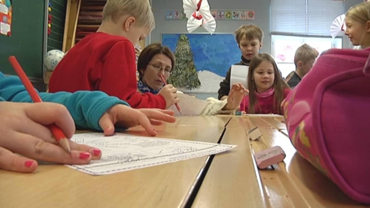 Opettaja neuvoo oppilaita vuodenaikatehtävässä pulpettien ääressä.