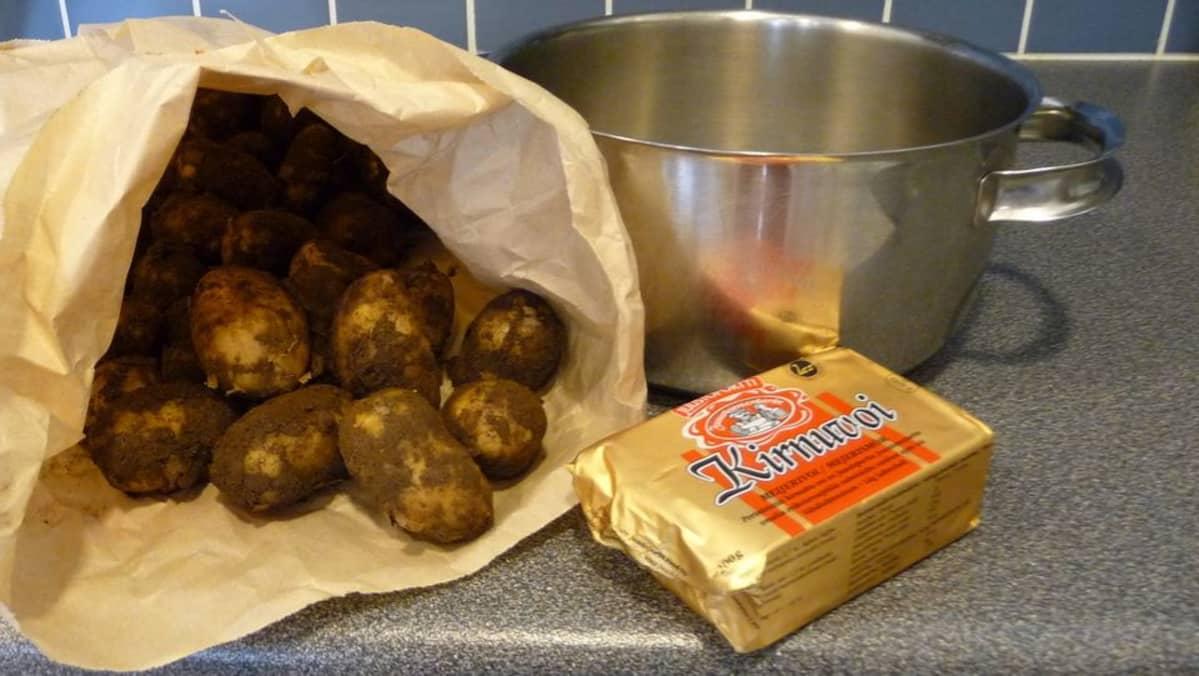 Multaisia perunoita paperipussissa tiskipöydällä, vieressä kattila ja voipaketti.