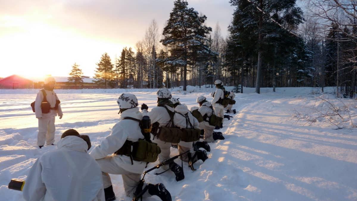 Kuvassa varusmiehiä harjoittelemassa lumipuvuissa.