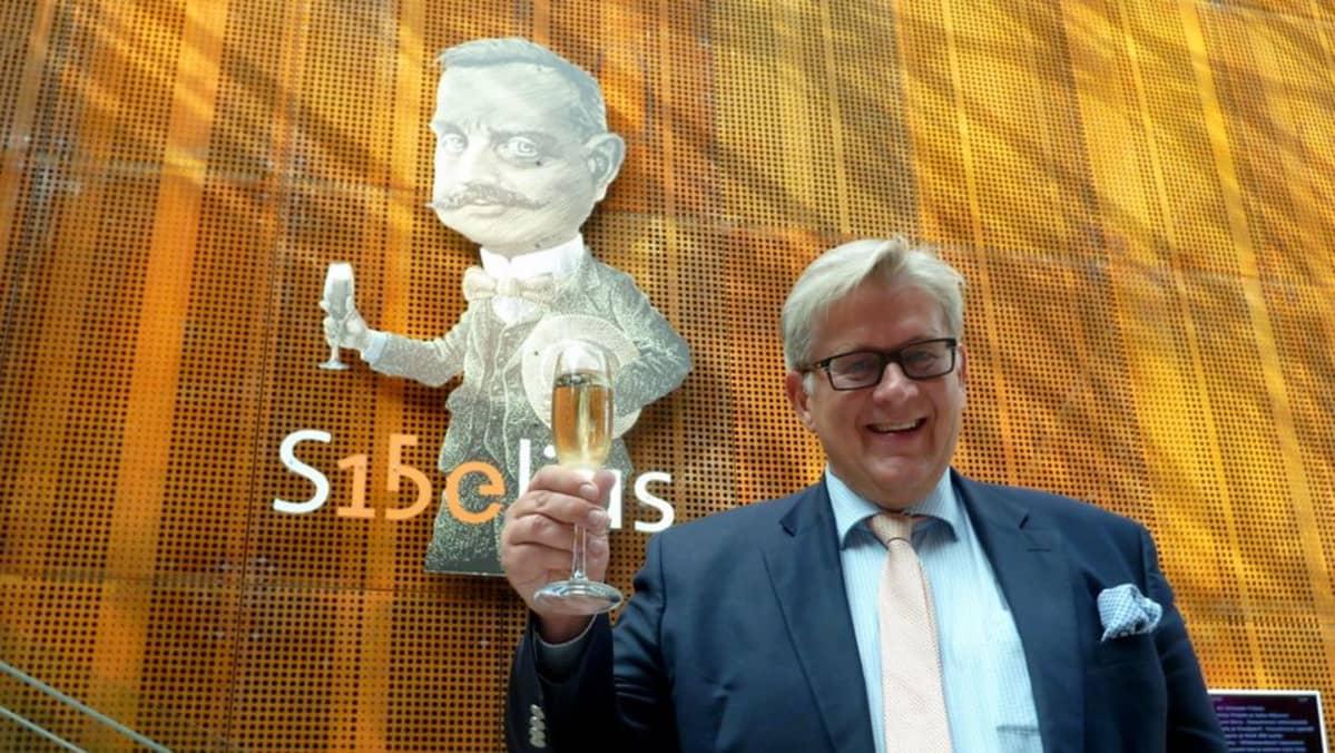 Erkki Korhonen lasi kädessä Sibelius-figuurin edessä