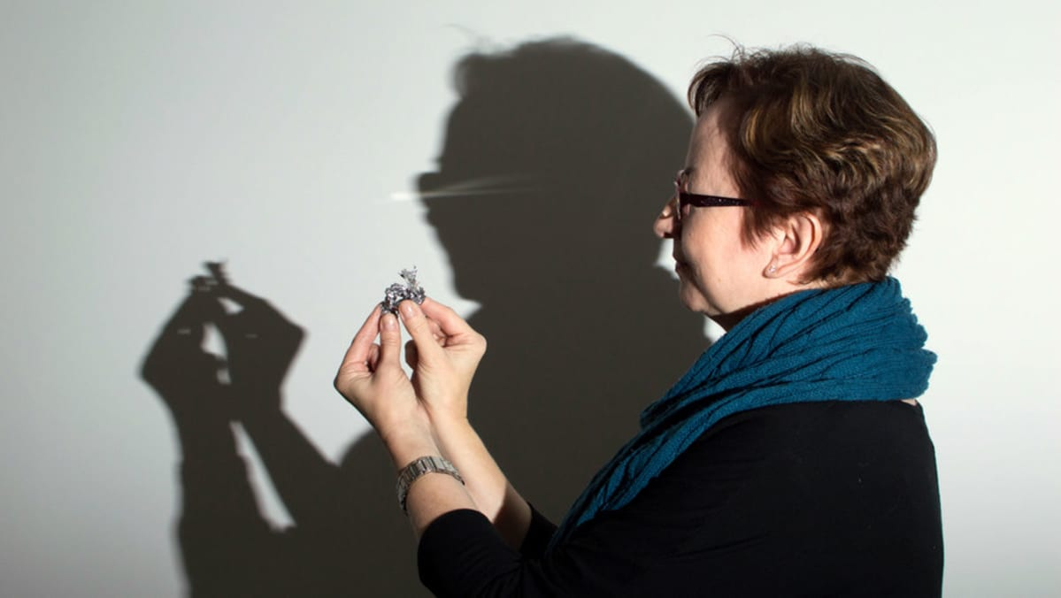 Tiina Ojutkangas pitelee kädessään uuden vuoden tinaa. Taustalla Ojutkankaan ja tinan varjo.