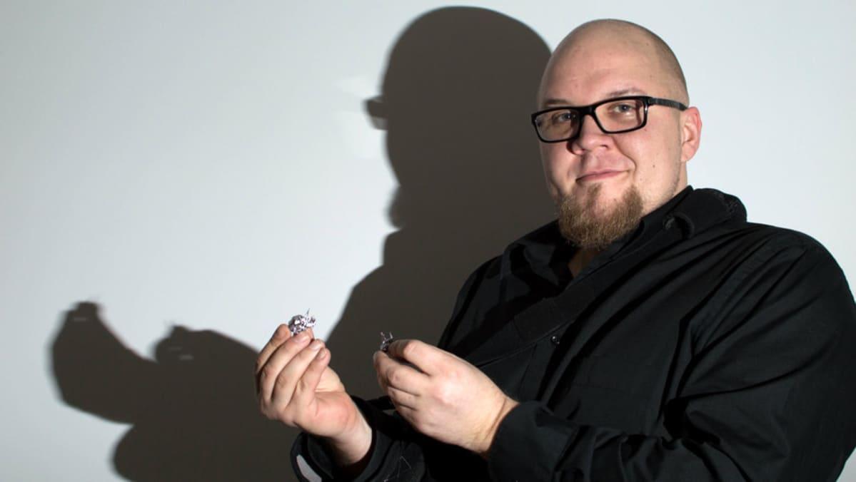 Jukka Holmstedt pitelee kädessään uuden vuoden tinaa. Taustalla tinan ja Holmstedtin varjo.