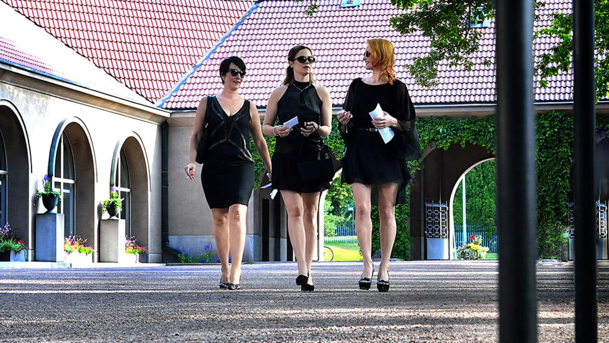 Kolme mustiin pukeutunutta naista kävelee aukion läpi.