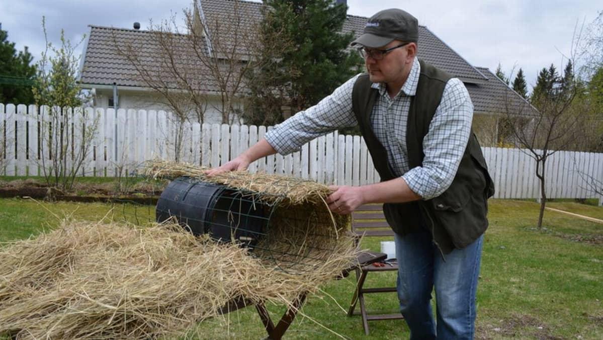 Mies tekee sorsalle tekopesää heinästä ja verkosta.