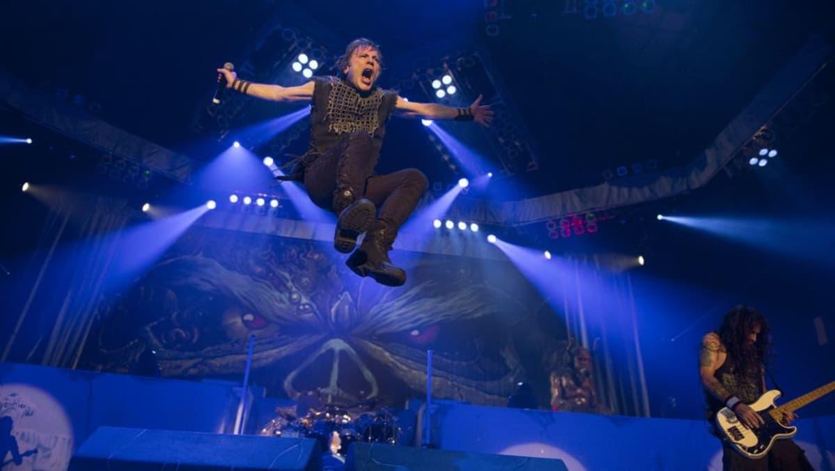 Mies hyppää rokkilavalla valojen loisteessa korkealle