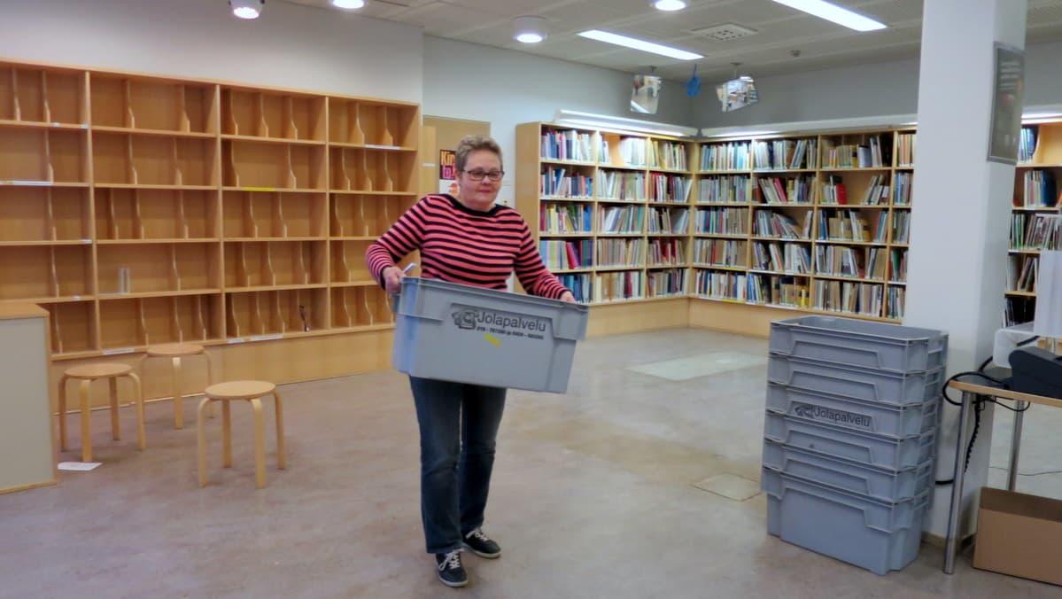 Nainen kantaa painavaa laatikkoa puolityhjässä kirjastohuoneessa