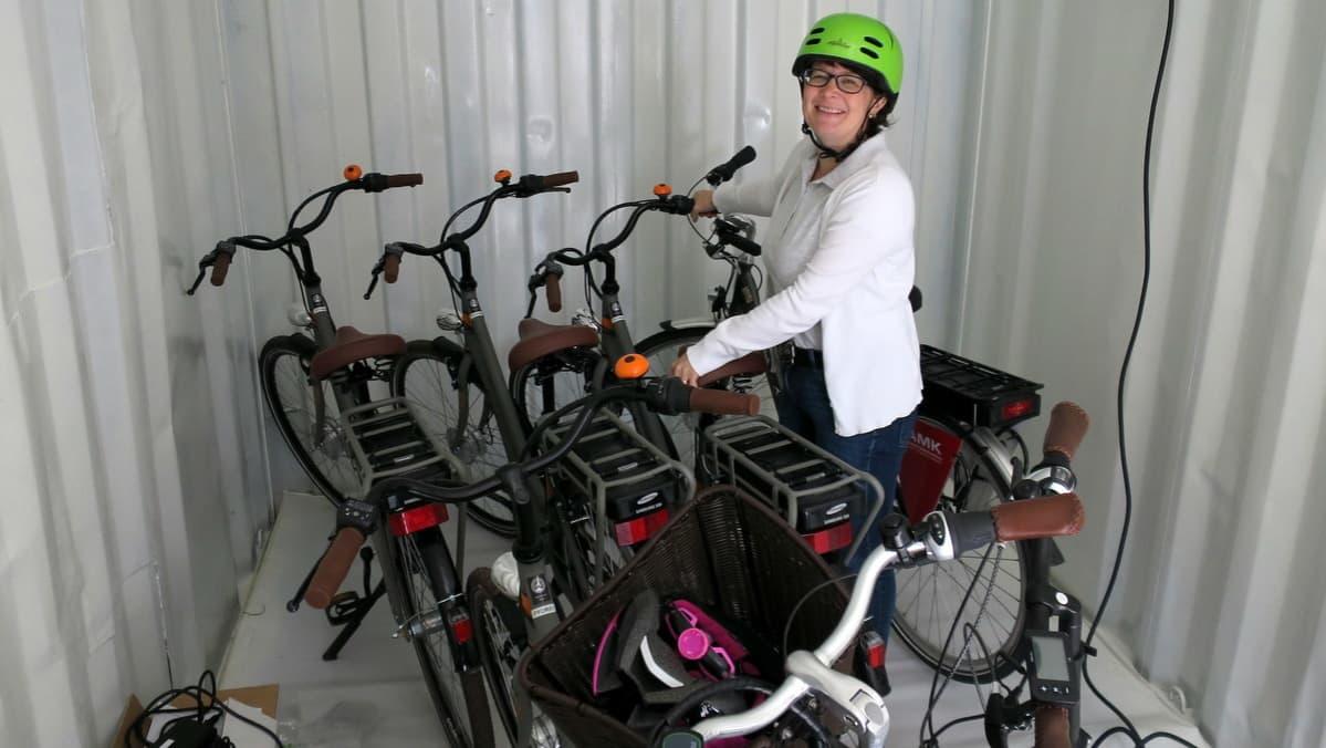 Nainen ottamassa sähköpyörää kontista käyttöönsä