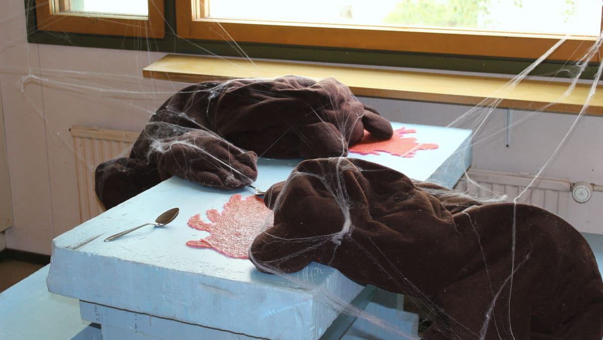 Anna Pekkalan teoksessa nalleperhe on kuolleena keittiön pöydän ääressä verilammikossa.