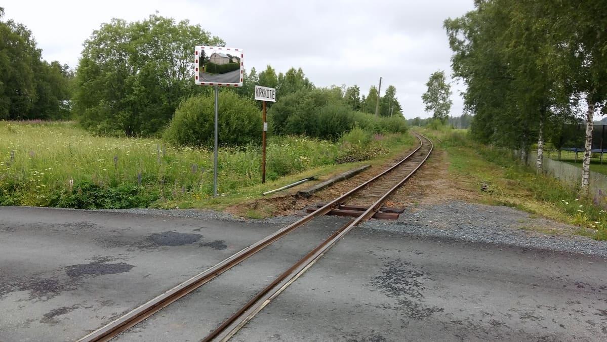 Asfalttitie ylittää kapearaiteiden rautatien