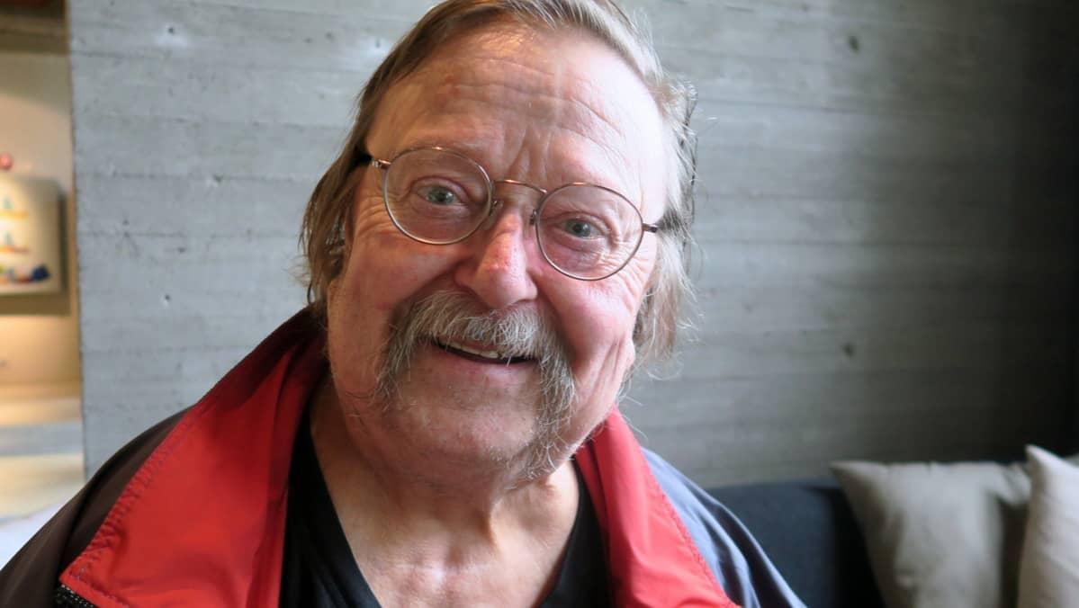 Vanhempi mies pyöreissä silmälaseissa ja mursuviikseillä katsoo kameraan