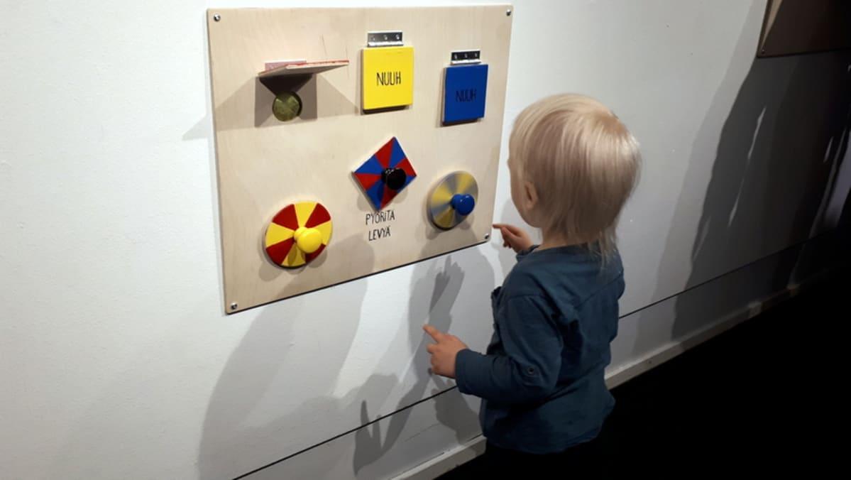Lapsi taidenäyttelyssä.