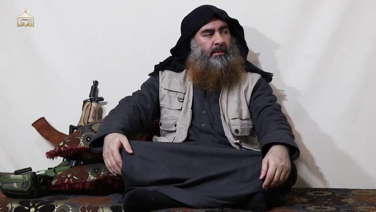 En man sitter i skräddarställning på golvet. Han har långt skägg och en svart huva på sig.