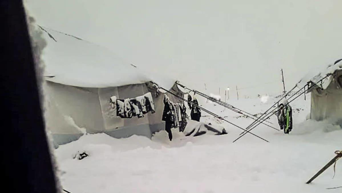 Snö på marken i al-Hol-lägret i Syrien. På bilden syns tält och kläder som händer utanför tälten. kläderna har också snö på sig.