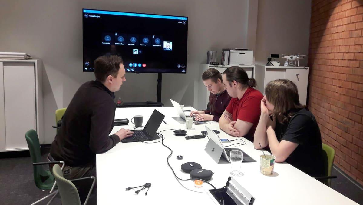 Miehiä toimistossa pöydän ympärillä