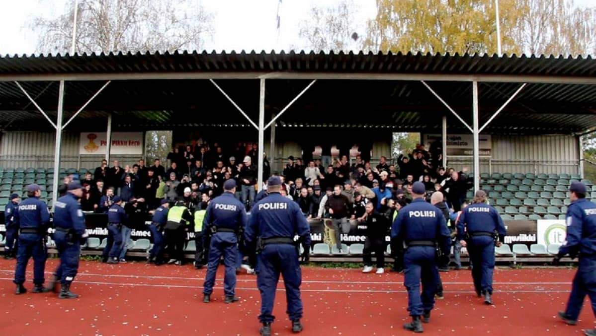 FC Lahden kannattajia katsomossa, poliiseja kentällä.