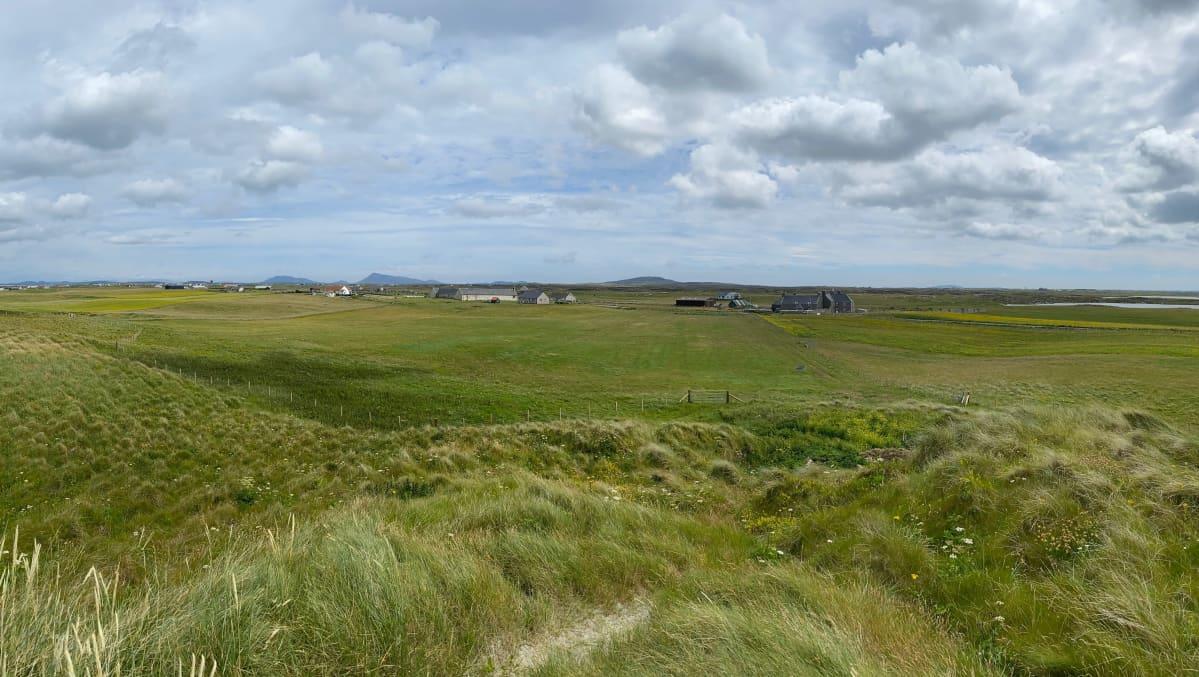 Maisemakuva Ulko-Hebrideiltä. Kuvassa vihreä niitty, asutusta kaukana ja pilviä taivaalla.