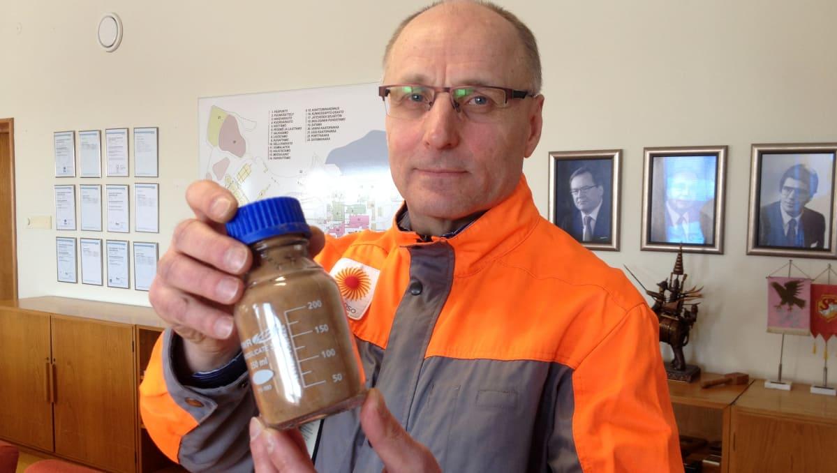 Kehitysjohtaja Jarmo Rinne esittelee kuivaligniinipurkkia