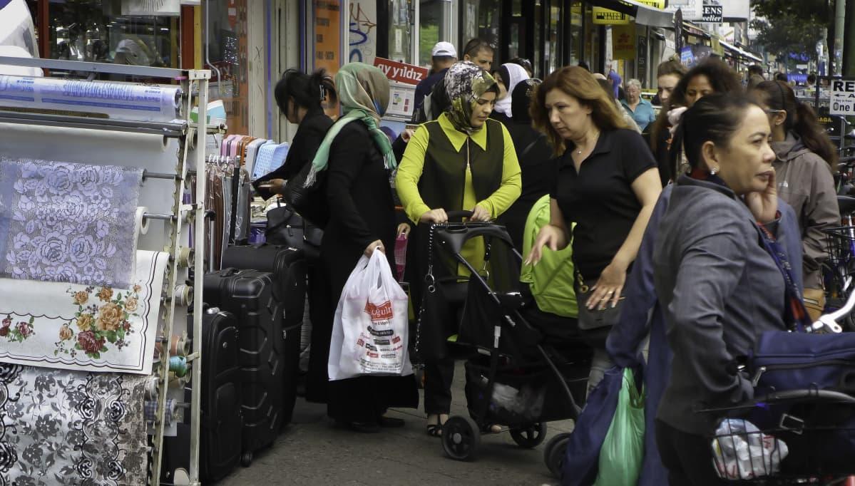 Kadulla on paljon naisia. Osalla on päässään islamilaiset huivit, osalla ei.  Kuvan keskellä lastenvaunuja työntävä huvipäinen nainen aiheuttaa ruuhkaa. Kadun reunassa myydään kangasta, matkalaukkuja ja muuta tavaraa.