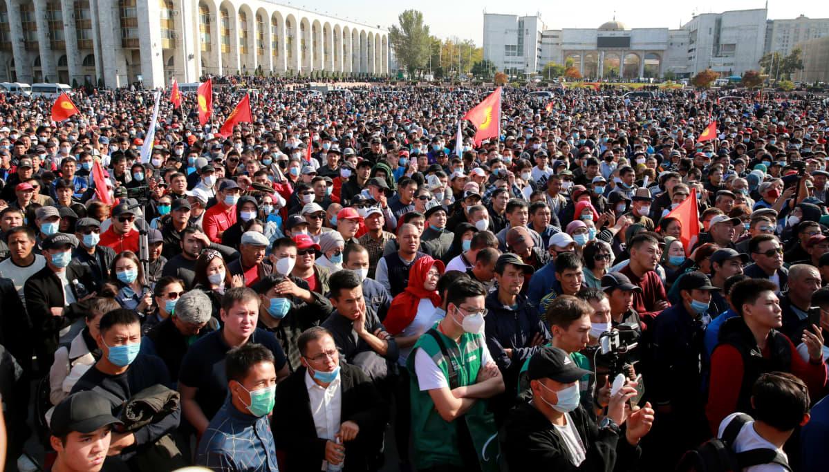 Suuri mielenosoittajajoukko aukiolla.