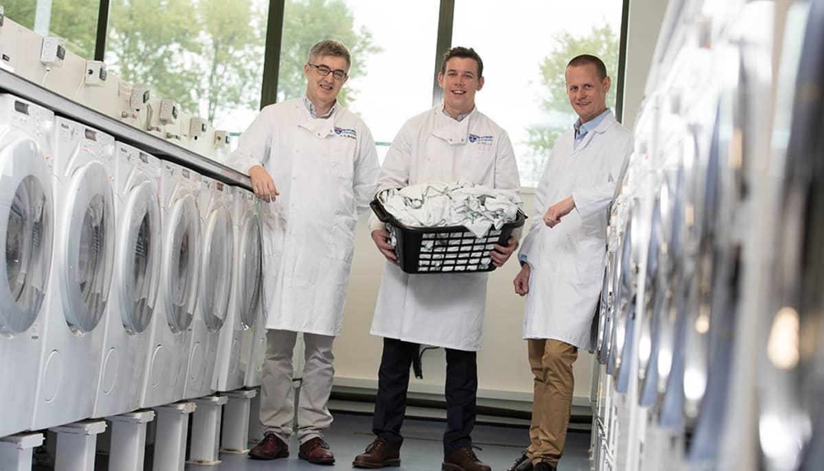 Kolme valkoisiin takkeihin pukeutunutta miestä kahden pyykkikonerivistön välissä. Keskimmäisellä miehellä on käsissään korillinen pyykkiä.