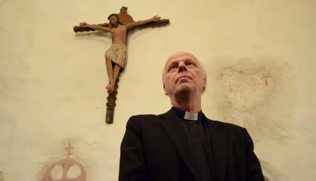 Pappi Reijo Sillanpää Vanajan kirkossa, taustalla krusifiksi