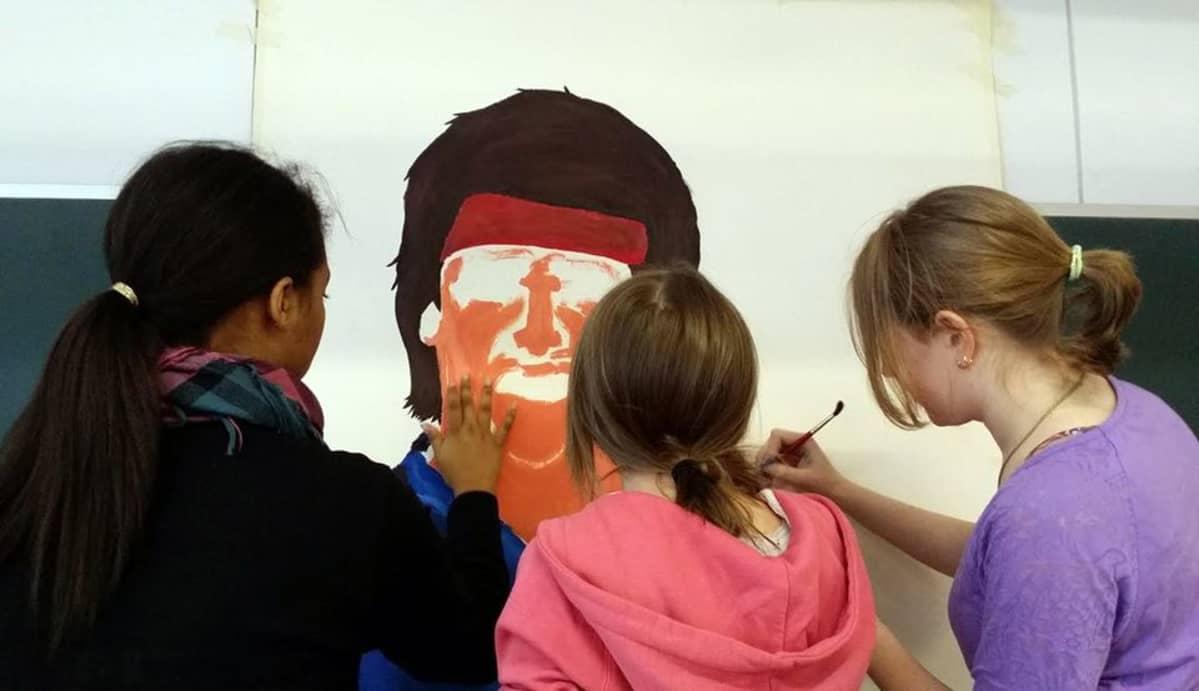 Kuvassa oppilaat maalaavat pahviin kuvaa laulaja Frederikistä.