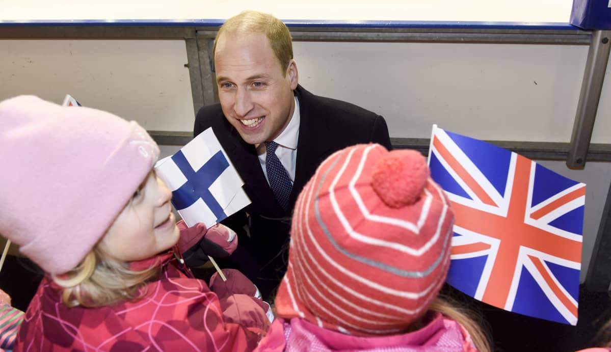 Prinssi William juttelee lapsille jotka pitävä suomen ja Englannin lippua