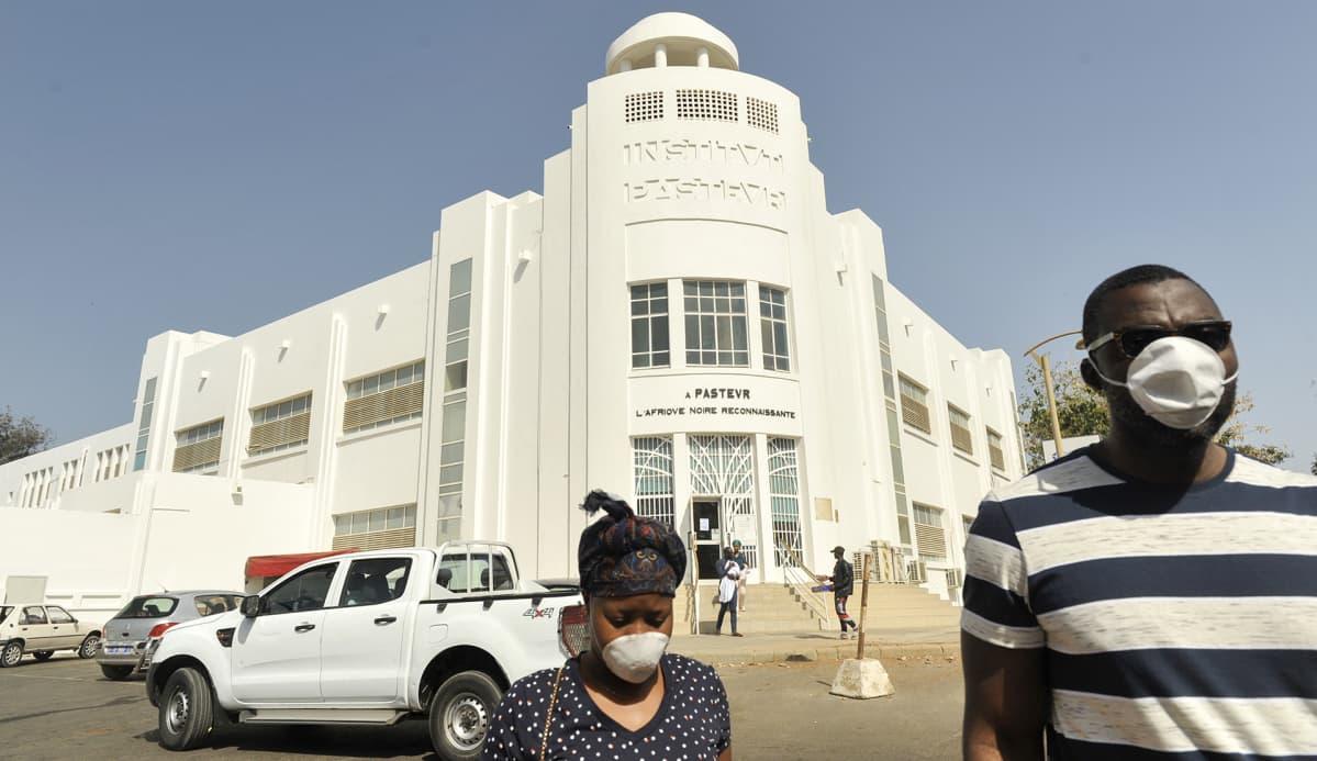 Ihmisiä kaduilla hengityssuojaimet kasvoillaan Dakarissa, Senegalissa 23. maaliskuuta.