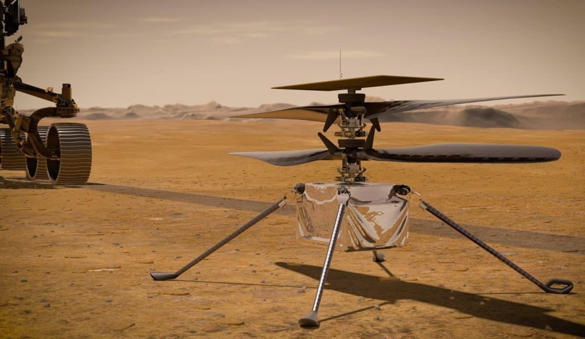 Neljällä pitkällä jalalla seisova laatikon muotoinen helikopteri Marsin punaisella pinnalla. Taustalla kuvasta rullaa pois mönkijä.