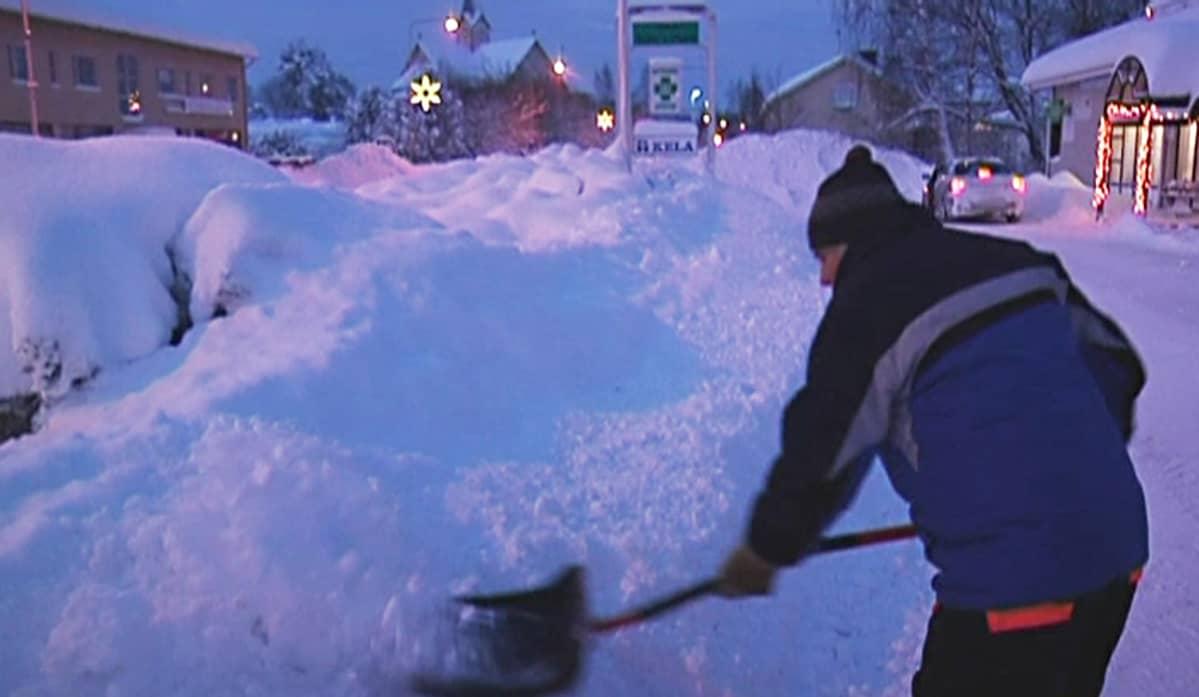 mies lapioimassa lunta