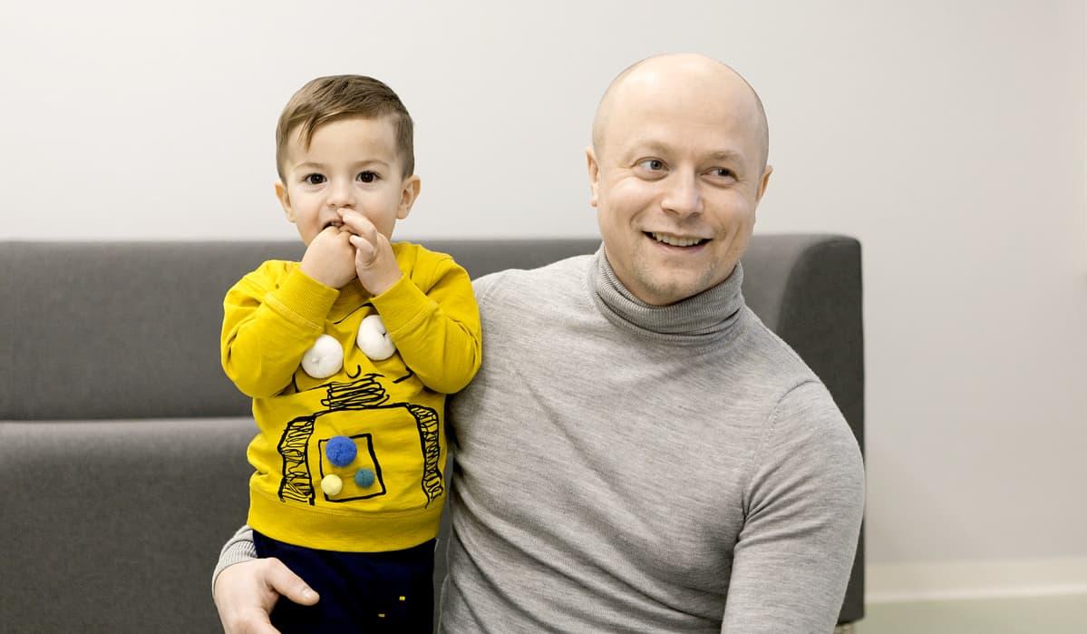 Ian Glavatski istuu poikansa kanssa Touhulan päiväkodin lattialla.