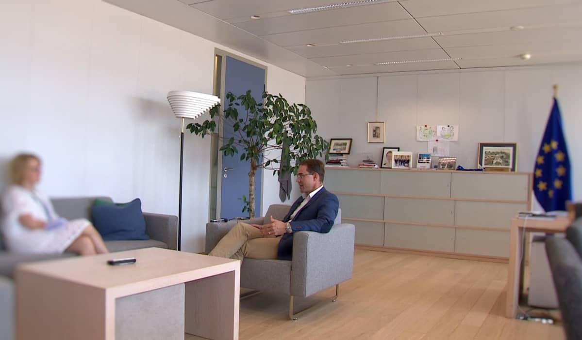 Jyrki Katainen keskustelee toimittajan kanssa toimistossaan.