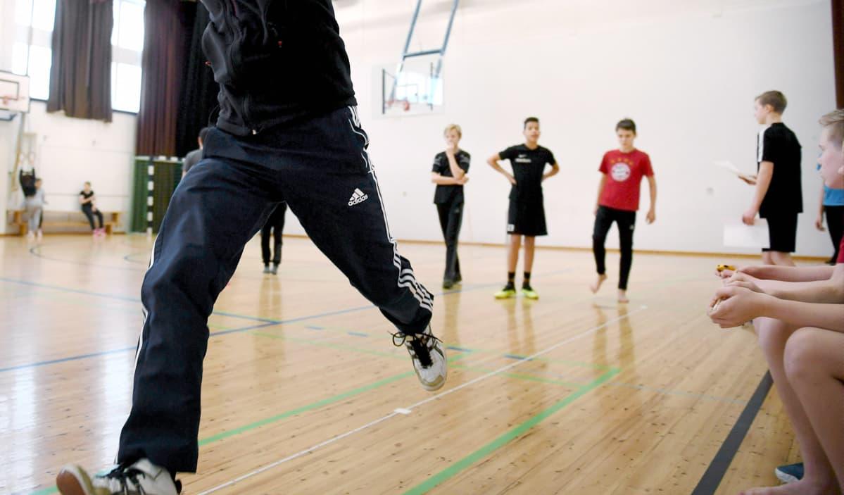 Liikunnanopettaja vetää liikuntatuntia peruskoulussa Helsingissä.