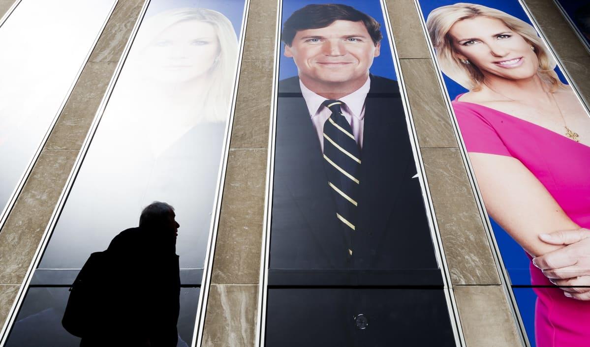 Fox Newsin ankkureita mainoksessa, mm. Tucker Carlson, mies kävelee mainoksen ohi.