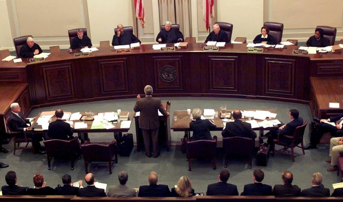 Laajassa kuvassa Floridan korkeimman oikeuden 6 tuomaria kuuntelee argumentoivaa miestä oikeussalissa.