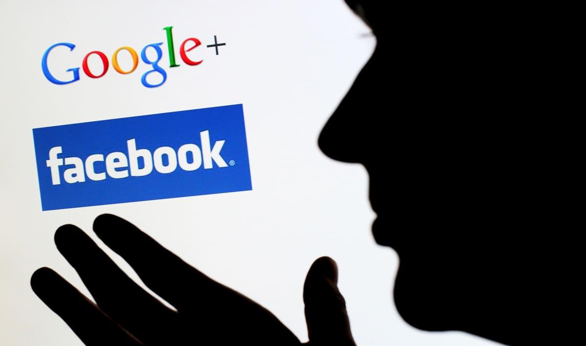 Ihmishahmo silhuettina näytön edessä, näytöllä Googlena ja Facebookin logot.