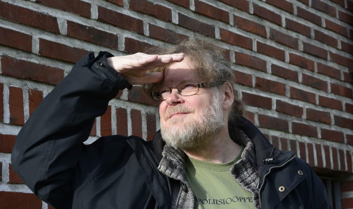 Kapellimestari Atso Almila estää kädellään aurinkoa häikäisemästä.