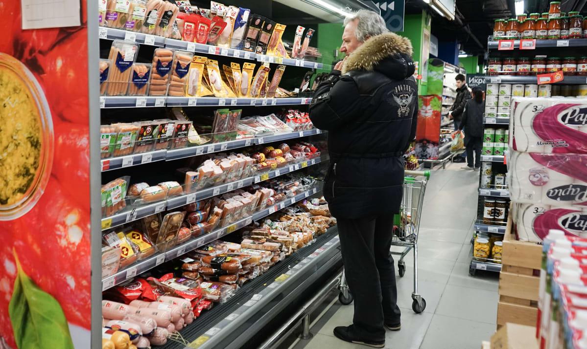 Mies kaupan kylmätiskillä katselee makkaroita