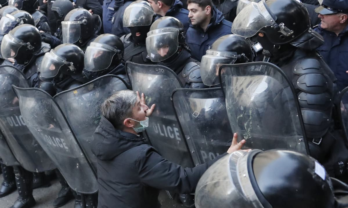 Mielenosoittaja kädet mellakkapoliisin kilpeä vasten.