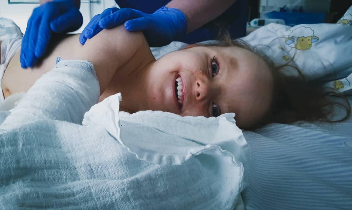 Hilda Tolonen nauraa sairaalasängyssä kun kumihanskoihin verhoutuneet kädet koskettavat hänen selkäänsä.