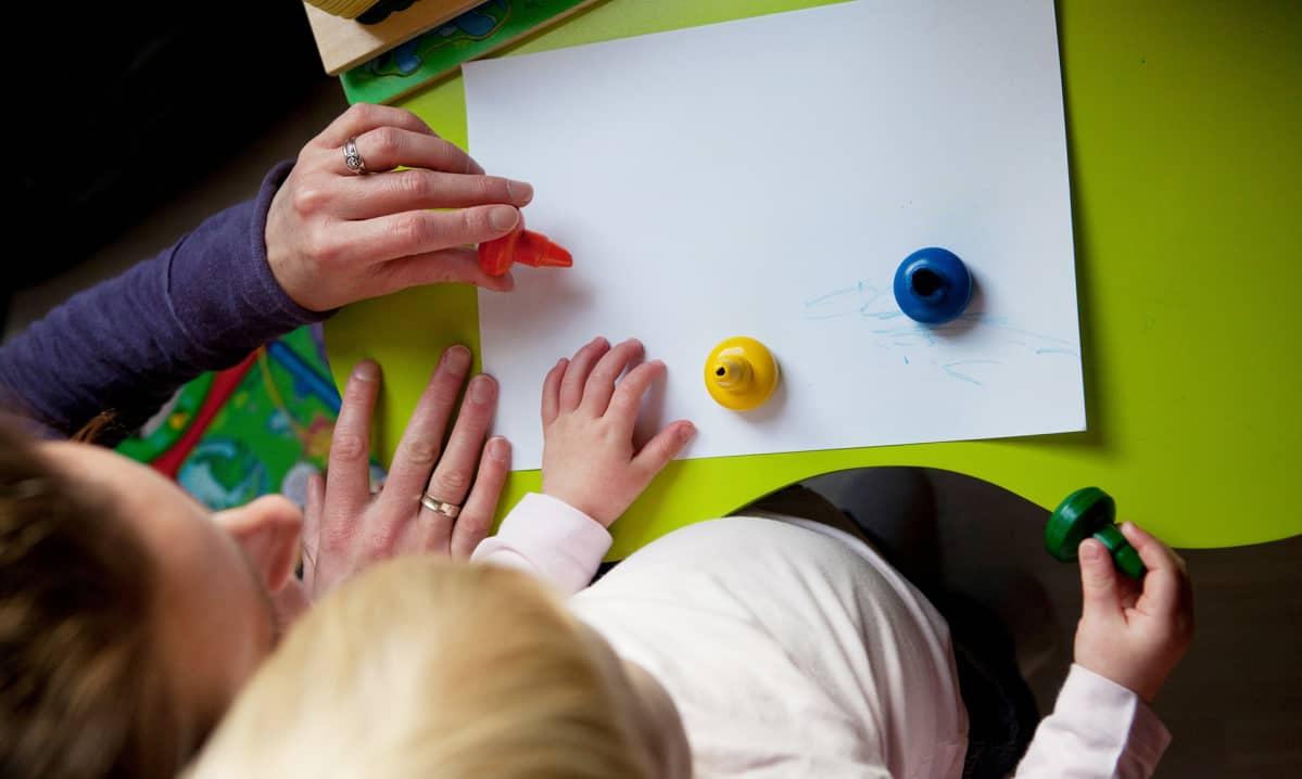 aikuinen ja lapsi piirtämässä