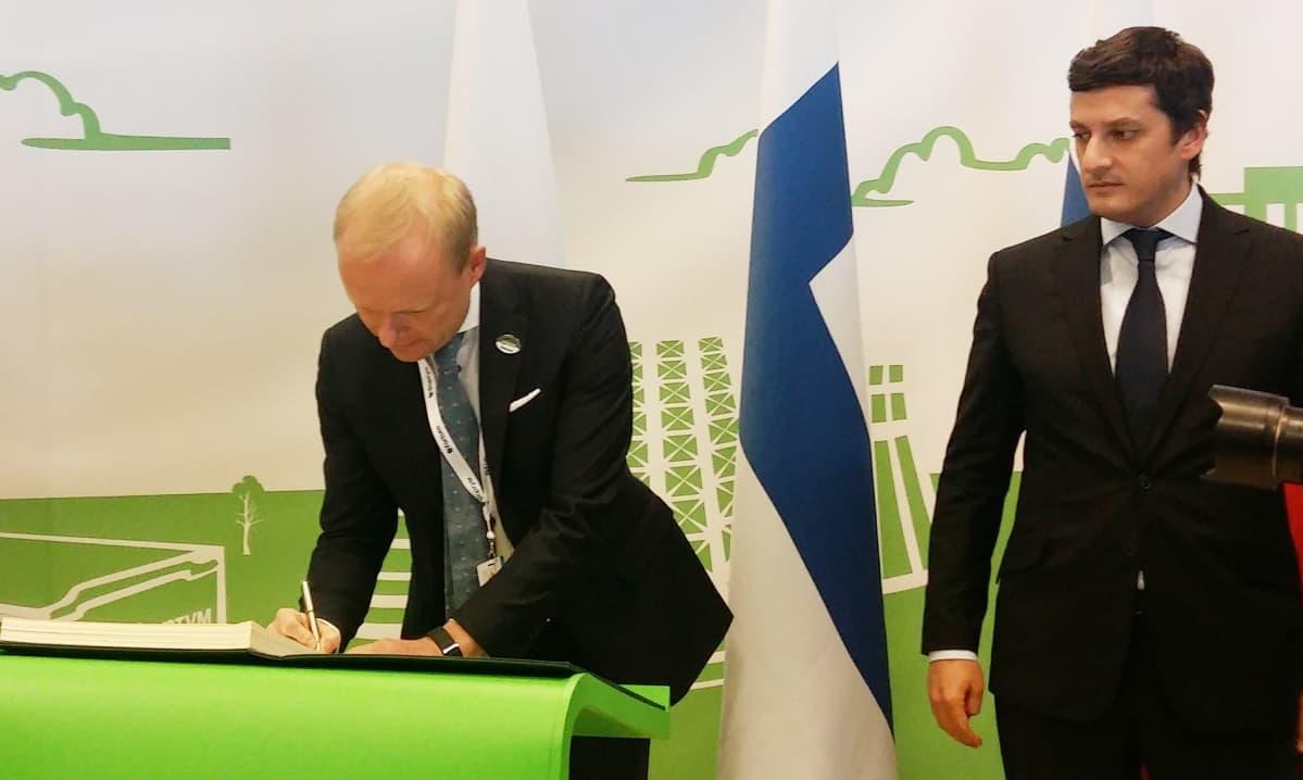 Fortumin pääjohtaja Pekka Lundmark kirjoittaa nimensä juhlakirjaan varaministeri Anton Inytsinin valvoessa.