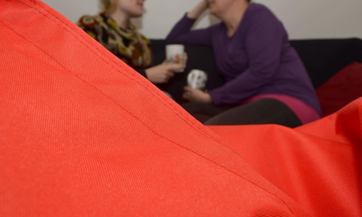 Kaksi naista sohvalla, kahvikupit kädessään.