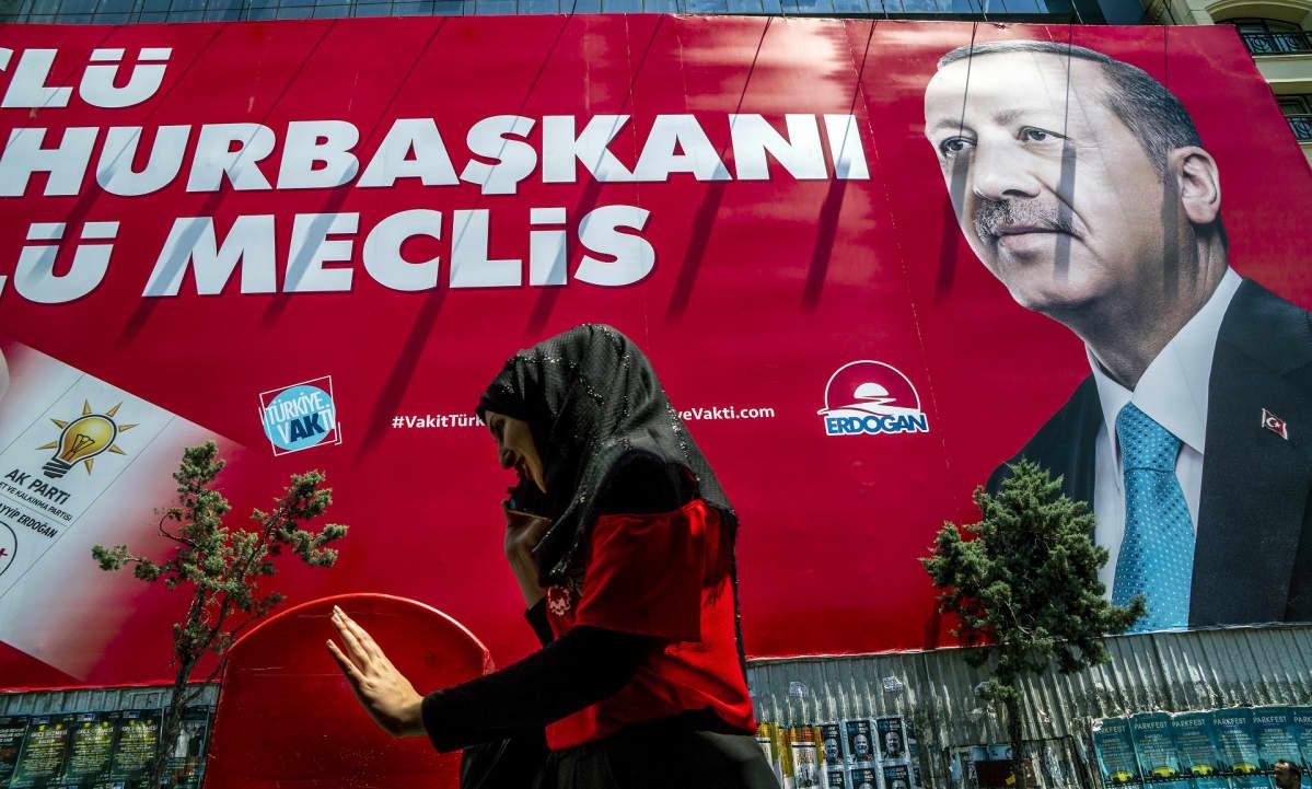 Nainen kävelee kadulla ja juttelee kännykkäänsä. Takana näkyy iso Recep Tayyip Erdoğanin punapohjainen kampanjajuliste.