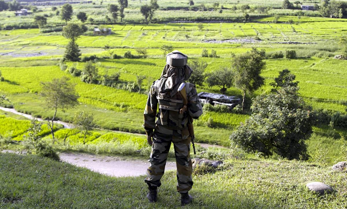 Intialainen sotilas seisoo maalaismaiseman edessä selkä kuvaajaan päin.